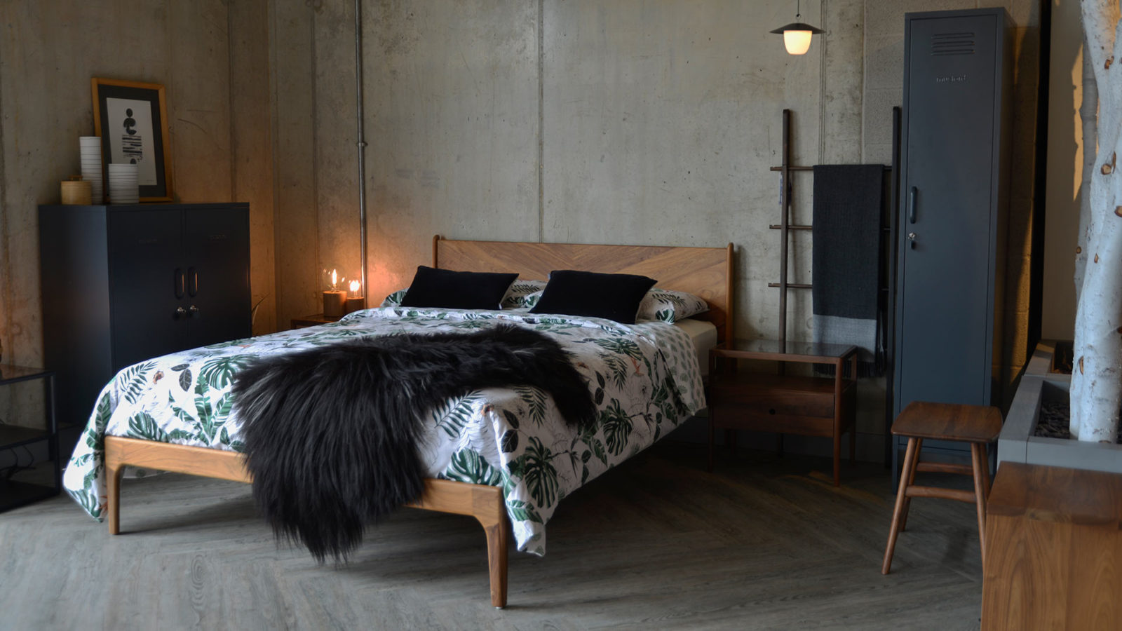 Industrial style bedroom featuring our hand made Hoxton bed in walnut with grey storage lockers and patterned bedding.