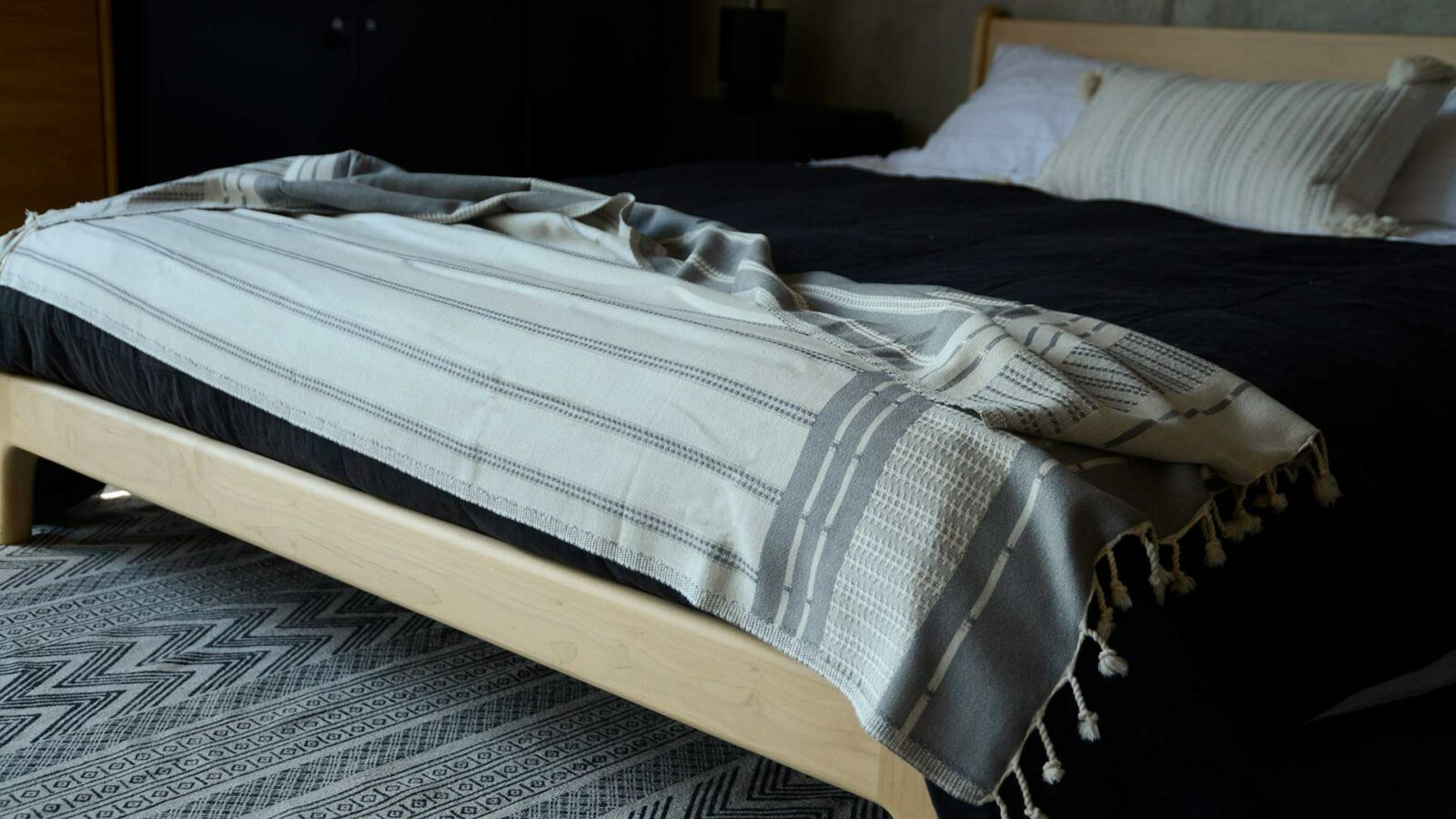 reversible woven cotton Turkish throw in ivory and grey shown on a low oak bed
