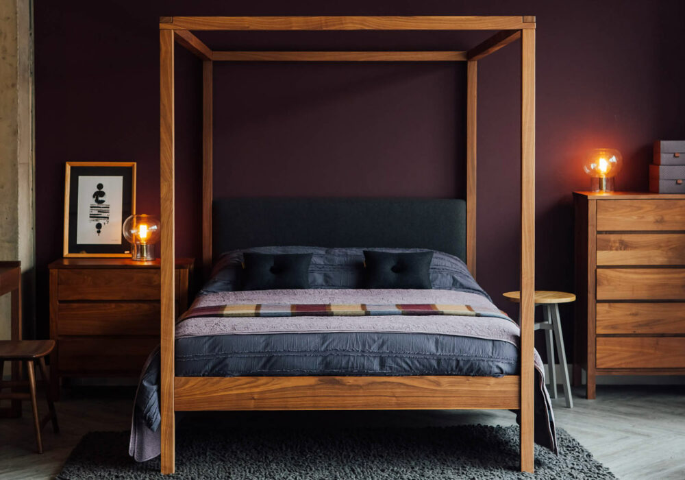 Autumnal bedroom with berry coloured wall, Walnut Highland 4 poster bed, and walnut drawers