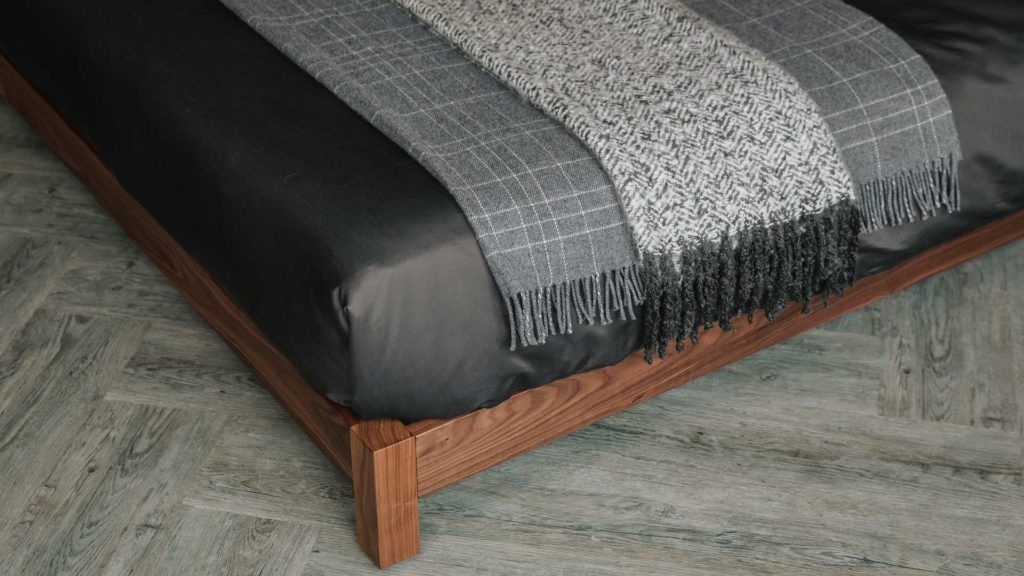 Detail view of Iona low bed foot and side rails with Grey and ivory throws on our luxury bedding