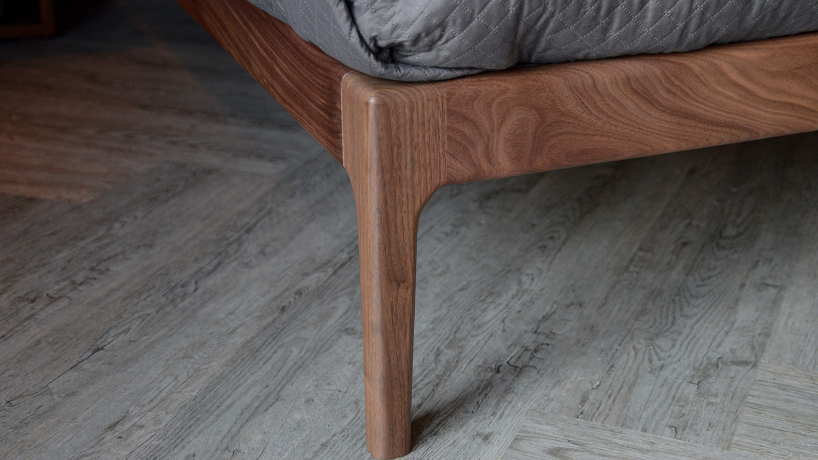 A closer view of the tapered leg of our solid walnut Hoxton bed