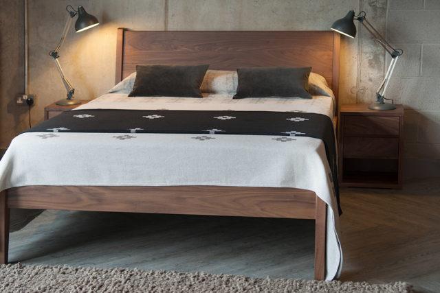 Cube bedside table shown with wooden Zanskar bed all in Walnut.